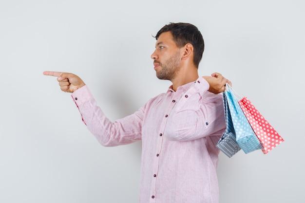 Jonge man in shirt met papieren zakken en wijzend op iets.