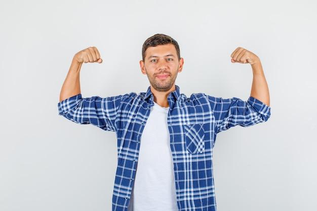 Jonge man in shirt met spieren van armen en op zoek naar sterke, vooraanzicht.