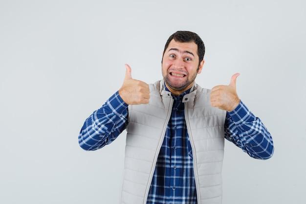 Jonge man in shirt, mouwloos jasje naar beneden gericht en nerveus, vooraanzicht.