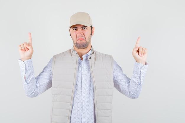 Jonge man in shirt, mouwloos jasje, pet en op zoek ontevreden. vooraanzicht.