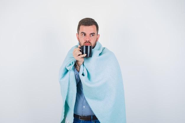 Jonge man in shirt, spijkerbroek, deken met beker terwijl hij wegkijkt en er knap uitziet, vooraanzicht.