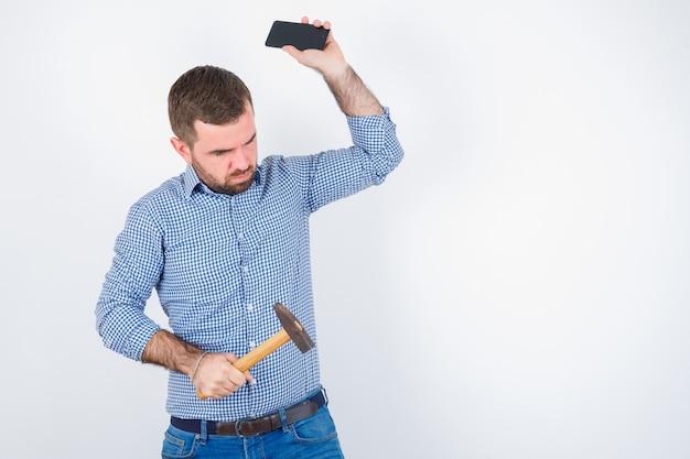 Jonge man in shirt, spijkerbroek die beweert mobiele telefoon weg te gooien terwijl hij hamer houdt en serieus kijkt, vooraanzicht.