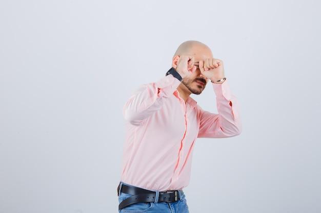 Jonge man in shirt, spijkerbroek die doet alsof hij zichzelf verdedigt en er bang uitziet, vooraanzicht.