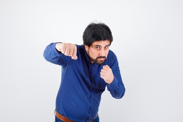 Jonge man in shirt, spijkerbroek die in vechthouding staat en er zelfverzekerd uitziet, vooraanzicht.