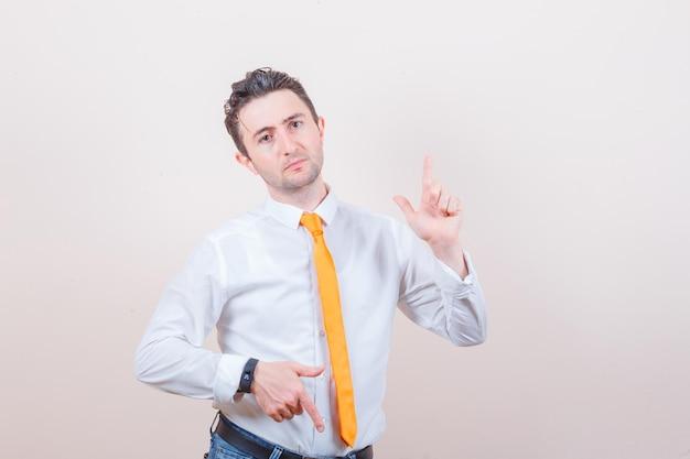 Jonge man in shirt, spijkerbroek die met de vingers op en neer wijst en besluiteloos kijkt looking