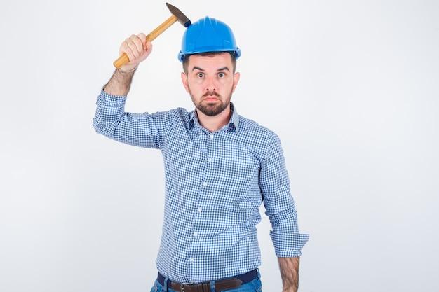 Jonge man in shirt, spijkerbroek, helm die zijn hoofd slaat met een hamer en er stom, vooraanzicht uitziet.