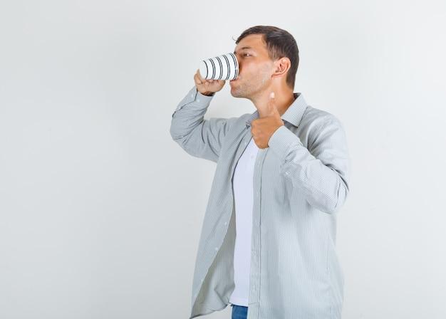 Jonge man in shirt, spijkerbroek koffie drinken met duim omhoog