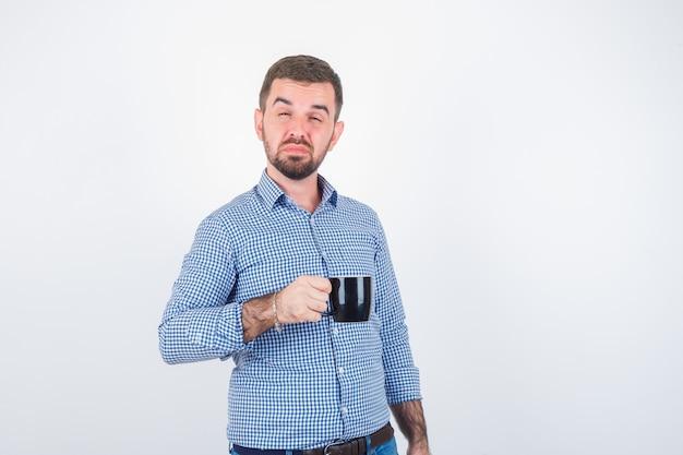 Jonge man in shirt, spijkerbroek ogen sluiten terwijl beker vast te houden en op zoek zelfverzekerd, vooraanzicht.