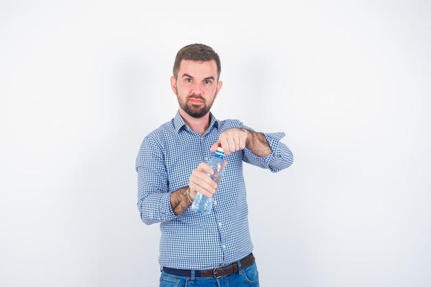 Jonge man in shirt, spijkerbroek plastic waterfles openen en op zoek zelfverzekerd, vooraanzicht.