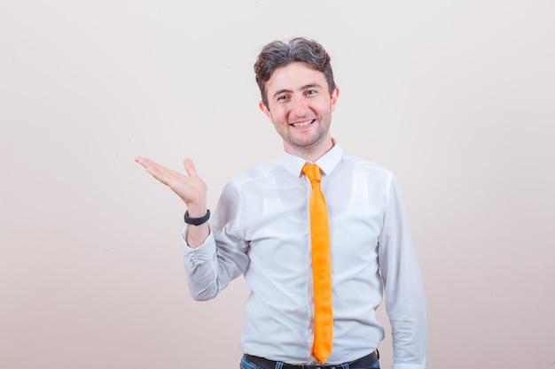 Jonge man in shirt, spijkerbroek spreidt handpalm opzij en ziet er vrolijk uit