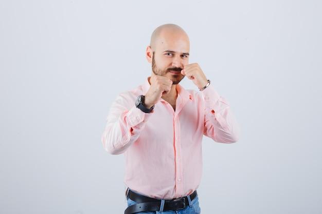 Jonge man in shirt, spijkerbroek staat in gevechtshouding en ziet er zelfverzekerd uit, vooraanzicht.