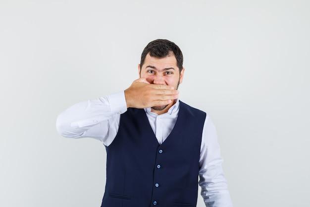 Jonge man in shirt, vest met hand over mond en op zoek geïrriteerd