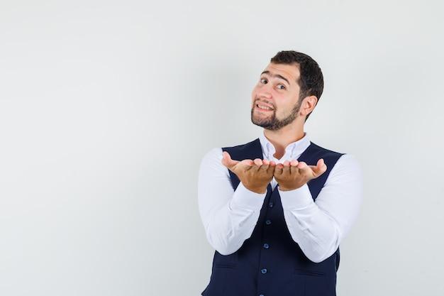 Jonge man in shirt, vest met palmen zoals iets presenteren en er vrolijk uitzien