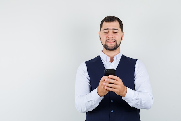 Jonge man in shirt, vest met tekstchat op smartphone