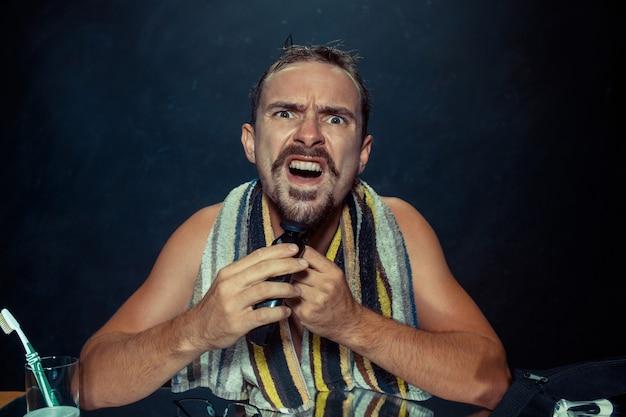 Jonge man in slaapkamer zit spiegel krabben zijn baard thuis. menselijke emoties en levensstijlconcept