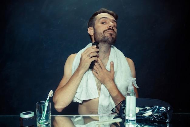 Jonge man in slaapkamer zit spiegel krabben zijn baard thuis