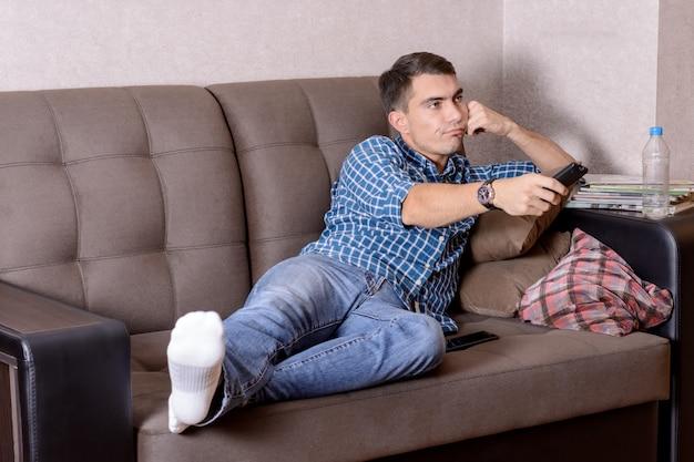 Jonge man in spijkerbroek, met een afstandsbediening voor de tv-verveling op het gezicht verandert het kanaal