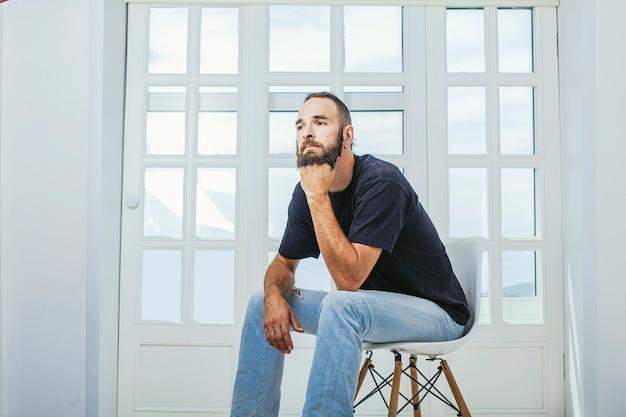 Jonge man in spijkerbroek met een baard een hipster zittend op een stoel op de achtergrond