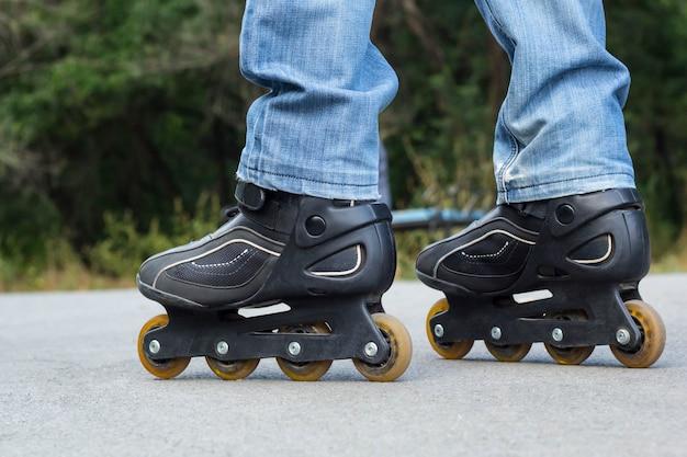 Jonge man in spijkerbroek rijden rolschaatsen in de stad. close-up benen