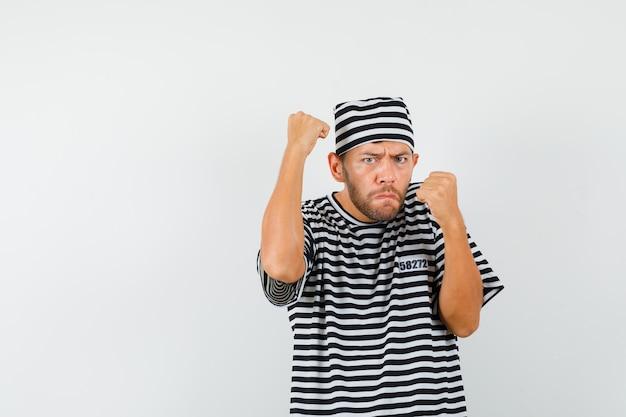 Jonge man in strijd pose in gestreept t-shirt, hoed en ziet er krachtig uit.