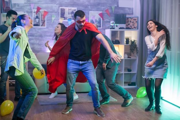 Jonge man in superheld kostuum dansen in het midden van de kamer. groep mensen dansen.