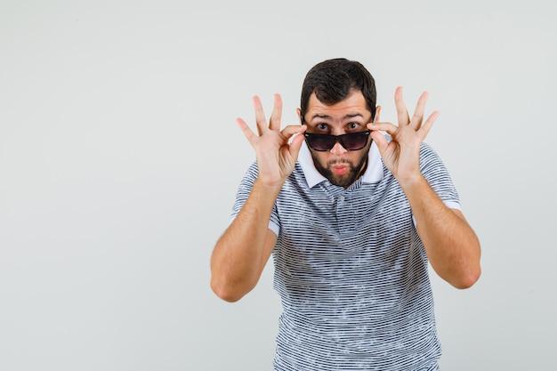 Jonge man in t-shirt bril opstijgen om duidelijk te zien en verbaasd kijken