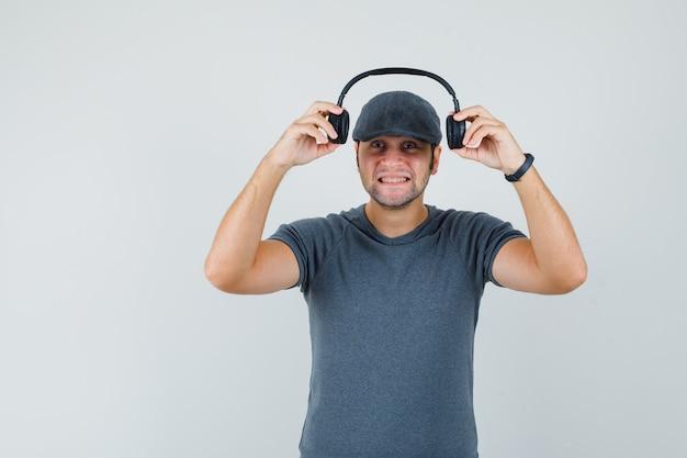 Jonge man in t-shirt cap koptelefoon opstijgen en vrolijk kijken