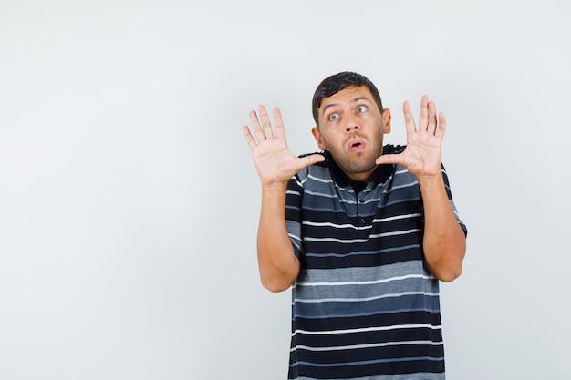 Jonge man in t-shirt die handen op preventieve wijze opheft en er bang uitziet, vooraanzicht.