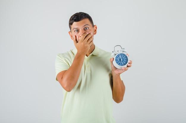 Jonge man in t-shirt die mond bedekt en wekker houdt en verbaasd kijkt