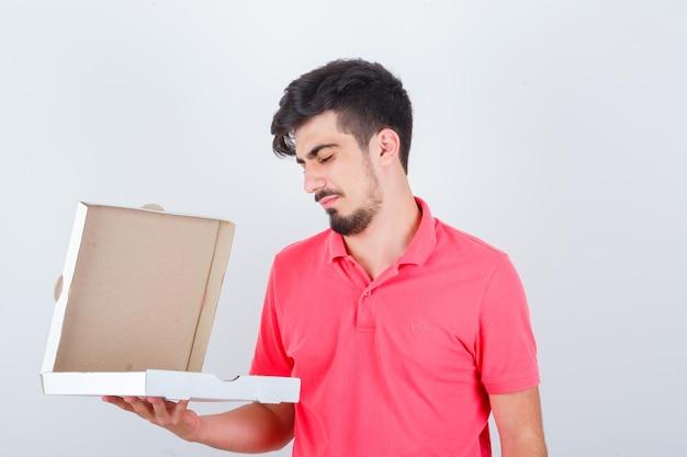 Jonge man in t-shirt die naar een geopende pizzadoos kijkt en aarzelend kijkt, vooraanzicht.