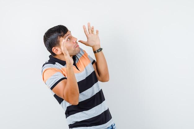 Jonge man in t-shirt die op preventieve wijze palmen opheft en bang kijkt