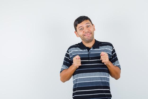 Jonge man in t-shirt die vijgengebaar toont en er grappig uitziet, vooraanzicht.