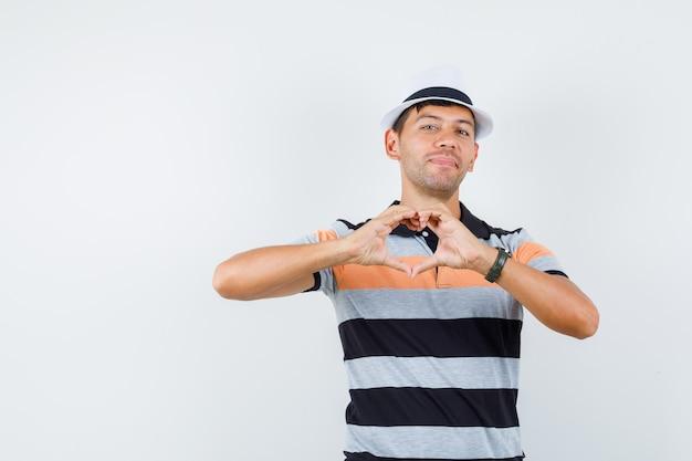 Jonge man in t-shirt en hoed die hartgebaar toont en vrolijk kijkt