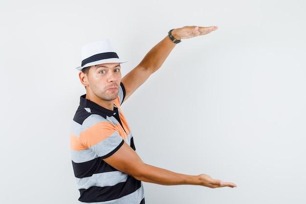 Jonge man in t-shirt en hoed met groot formaat bord