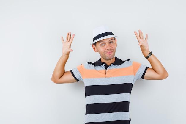 Jonge man in t-shirt en hoed poseren met opgeheven handpalmen en ziet er vrolijk uit