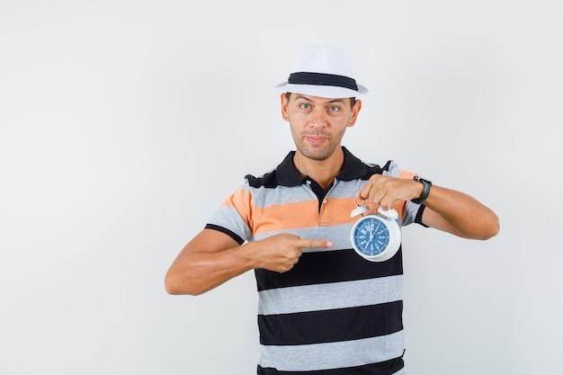 Jonge man in t-shirt en hoed wijzend op wekker en punctueel op zoek