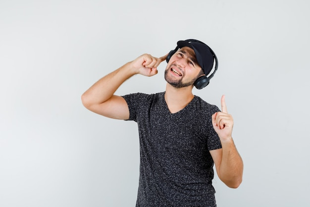 Jonge man in t-shirt en pet luisteren naar muziek met vinger omhoog en op zoek opgetogen