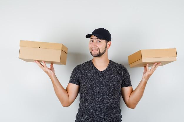 Jonge man in t-shirt en pet met kartonnen dozen en op zoek vrolijk