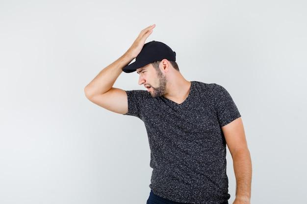 Jonge man in t-shirt en pet, spijkerbroek hoofd leunend op opgeheven hand en op zoek sorry