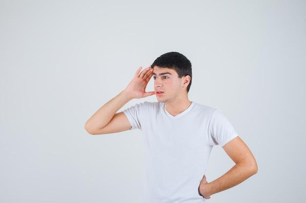 Jonge man in t-shirt hand boven het hoofd en op zoek gericht, vooraanzicht.