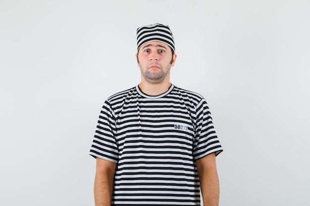 Jonge man in t-shirt, hoed camera kijken en bang, vooraanzicht kijken.