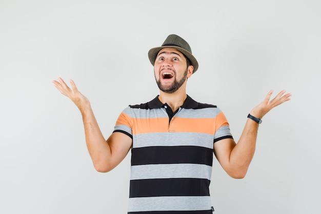 Jonge man in t-shirt, hoed die handen opheft terwijl hij omhoog kijkt en vrolijk, vooraanzicht kijkt.