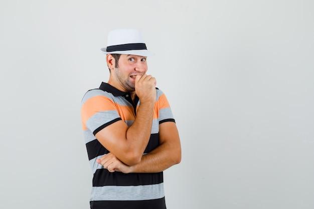 Jonge man in t-shirt, hoed die stiekem glimlacht en er grappig uitziet