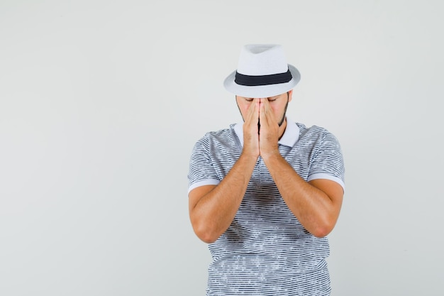 Jonge man in t-shirt, hoed hand in hand in biddend gebaar en stil, vooraanzicht.