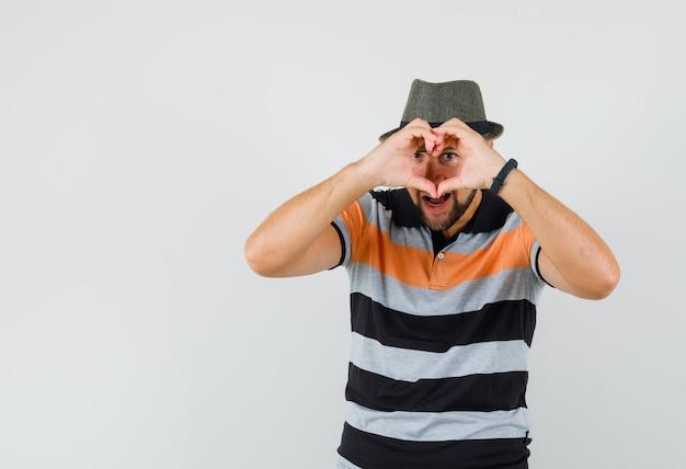 Jonge man in t-shirt, hoed met hartgebaar en op zoek naar geliefde, vooraanzicht.