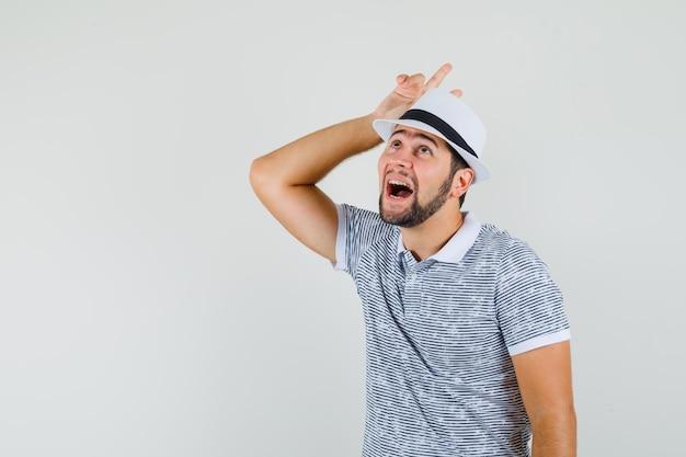 Jonge man in t-shirt, hoed met v-teken boven het hoofd als hoorns en ziet er grappig uit, vooraanzicht.