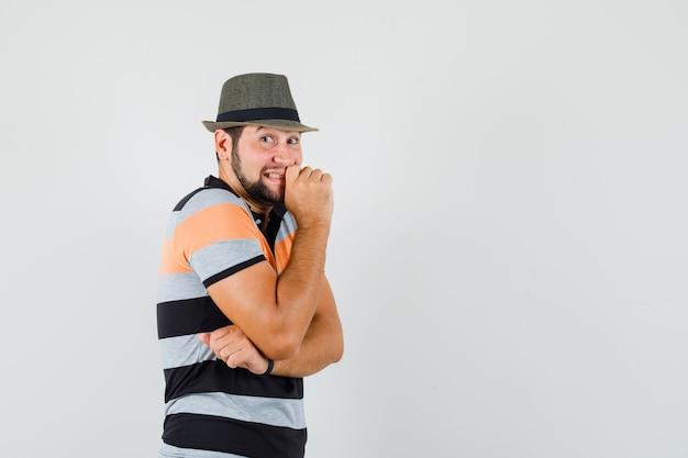 Jonge man in t-shirt, hoed staande in denken pose en op zoek vrolijk, vooraanzicht.