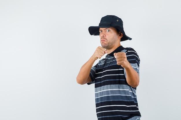 Jonge man in t-shirt, hoed staat in bokserhouding en ziet er krachtig uit, vooraanzicht.