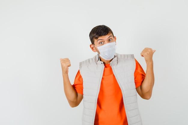 Jonge man in t-shirt, jas, masker met dubbele duimen naar achteren, vooraanzicht.