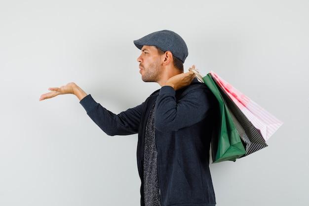 Jonge man in t-shirt, jas, pet met boodschappentassen, luchtkus verzenden.